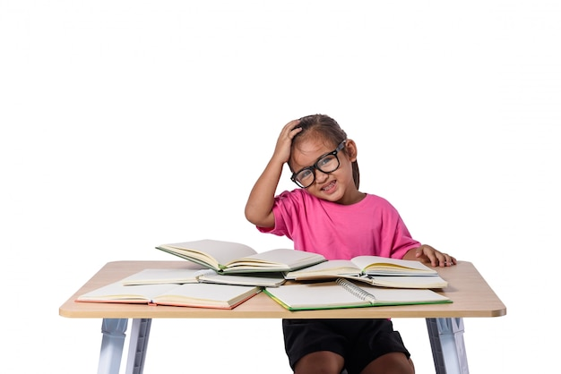 Little girl with glasses thought and many book on table. back to school concept, isolated on white