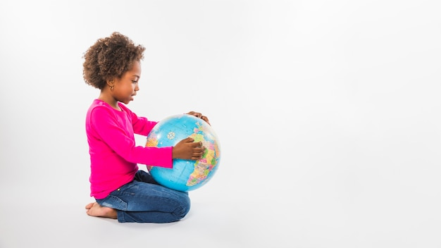 Little girl with globe in studio