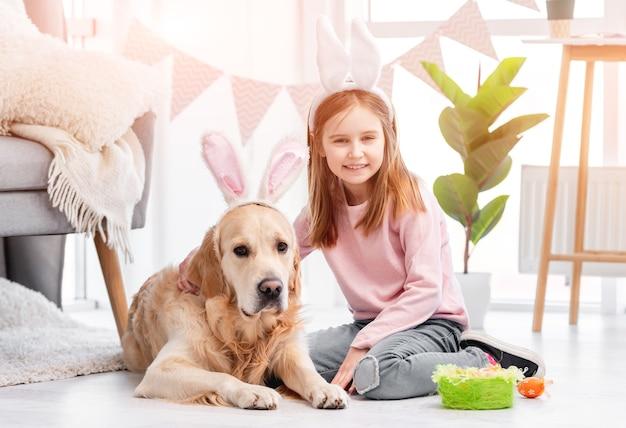 바닥에 앉아 부활절 장식 방에서보고 토끼 귀를 입고 골든 리트리버 강아지와 어린 소녀