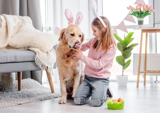 부활절 날에 집에서 바닥에 앉아 토끼 귀를 입고 골든 리트리버 강아지와 어린 소녀