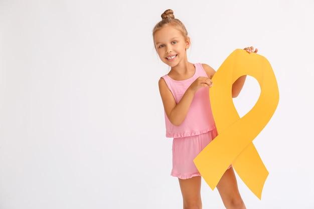 Маленькая девочка с золотой лентой. концепция осведомленности о детском раке