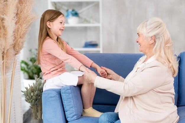 ソファに座っているおばあちゃんを持つ少女