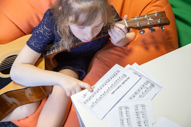 A little girl with a guitar learns solfeggio, sheet music and music theory.