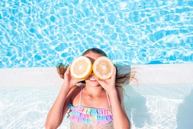 Little girl with halves citrus lemons in swimming pool