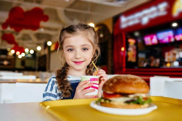 Маленькая девочка с гамбургером и газированным напитком