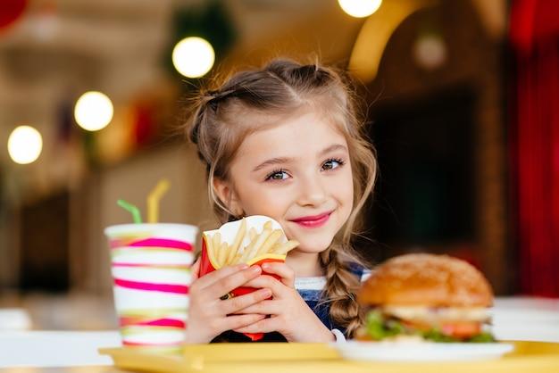 Маленькая девочка с гамбургером, газированным напитком и картофелем фри