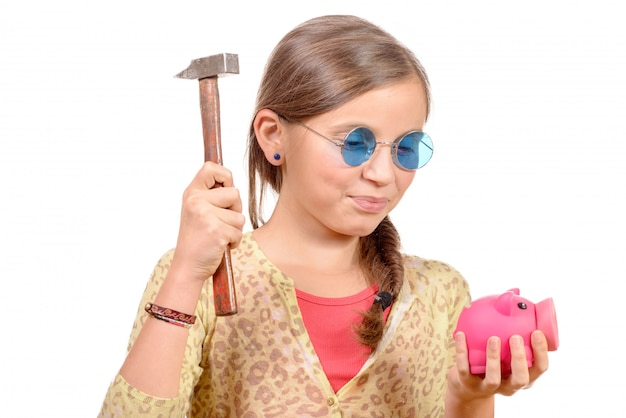 Little girl with hammer and piggy bank