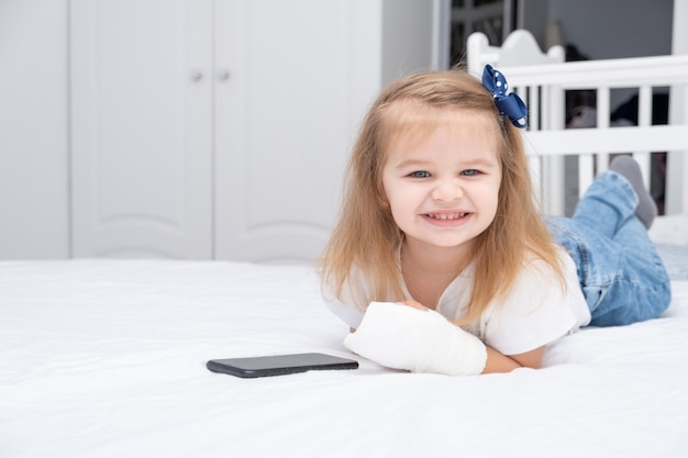 Little girl with hand in cast laying in bed using smartphone, watching cartoon or education video.