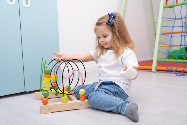 Little girl with hand in cast playing in wooden toys at home.