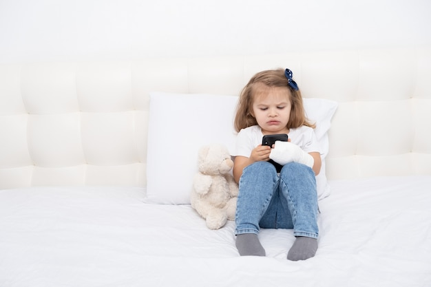 Little girl with hand in cast sitting in bed using smartphone, watching cartoon or education video.