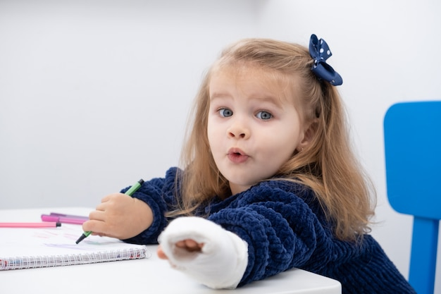 Little girl with hand in cast sitting at table trying draw with markers.