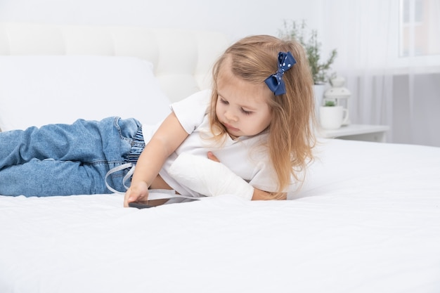 Маленькая девочка с рукой в гипсе, лежа в постели, используя смартфон, просматривая мультфильм или образовательное видео.