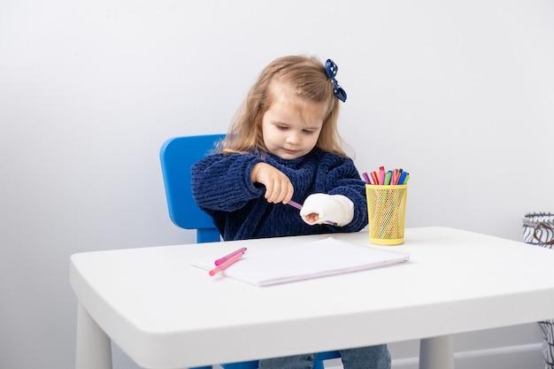 マーカーで描画しようとしているテーブルに座ってキャストで手を持つ少女。