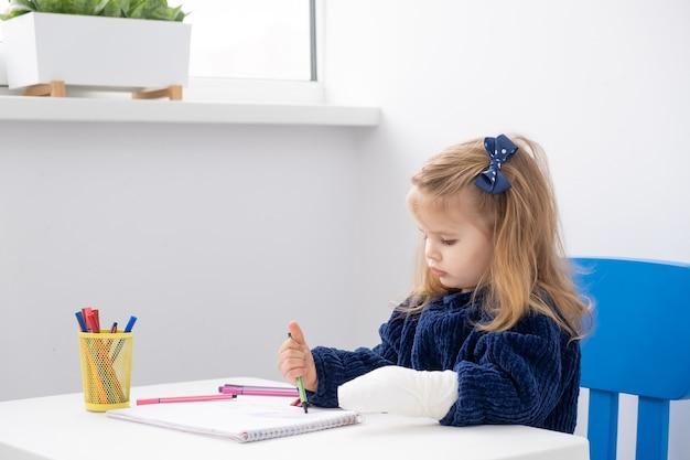 Маленькая девочка с рукой в гипсе, сидя за столом, пытается нарисовать маркерами.