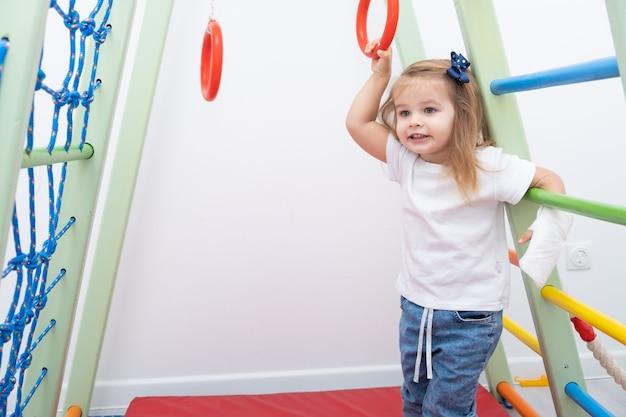 Маленькая девочка с рукой в гипсе, используя спортивный комплекс дома.