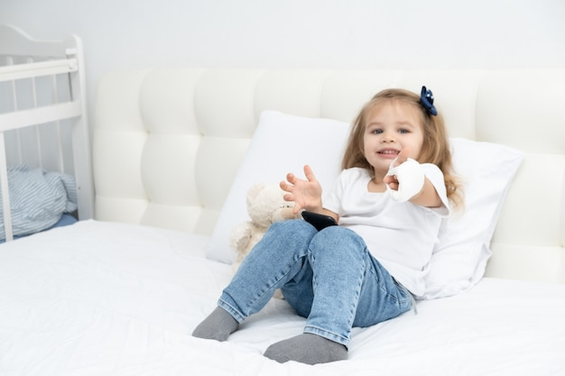 Little girl with hand in plaster sitting in bed showing the class, using smartphone.