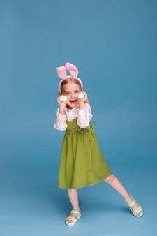 토끼 귀와 파란색 표면에 닭고기 달걀 어린 소녀. 부활절