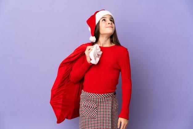 Маленькая девочка в шляпе и рождественском мешке изолирована на фиолетовом фоне и смотрит вверх