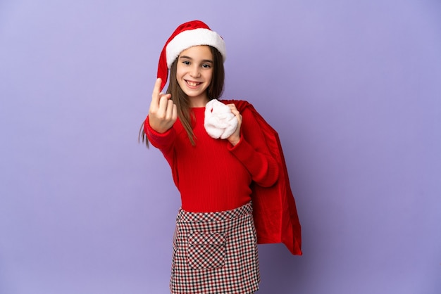 来るジェスチャーをしている紫色の背景に分離された帽子とクリスマスの袋を持つ少女