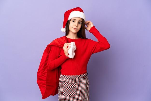 Маленькая девочка в шляпе и рождественский мешок, изолированные на фиолетовом фоне, сомневаясь