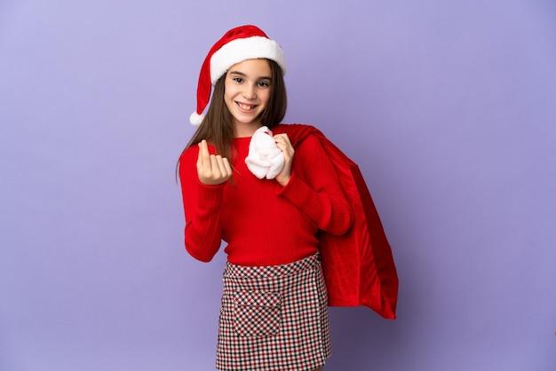 모자와 돈 제스처를 만드는 보라색 배경에 고립 된 크리스마스 자루 어린 소녀