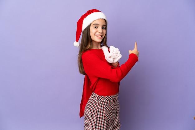 Маленькая девочка в шляпе и рождественский мешок, изолированные на фиолетовом фоне, указывая назад