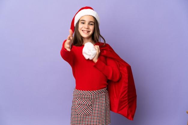 帽子とクリスマスの袋を持つ少女は、かなりの取引を閉じるために握手する紫色の背景に分離されました
