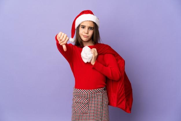 Маленькая девочка в шляпе и рождественском мешке изолирована на фиолетовом фоне, показывая большой палец вниз с негативным выражением лица