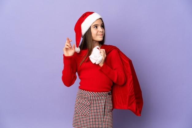 帽子とクリスマスの袋を持つ少女は、指が交差し、最高を願って紫色の背景に分離されました