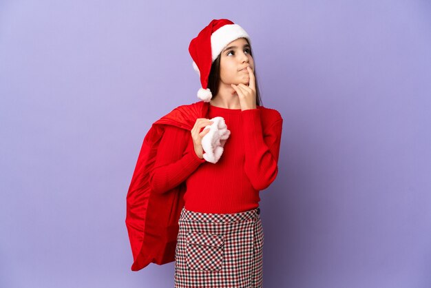 모자와 크리스마스 자루를 찾는 동안 의심을 갖는 보라색 벽에 고립 된 어린 소녀