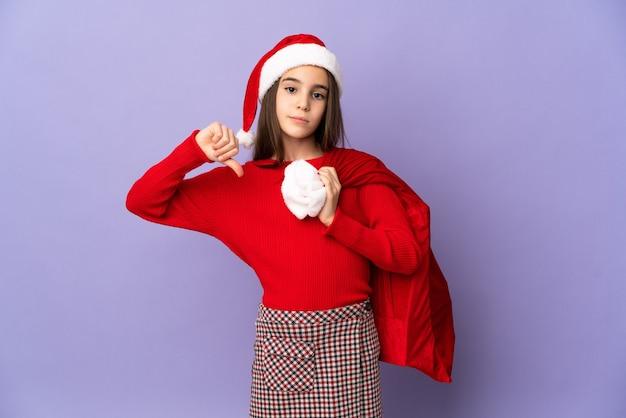 否定的な表現で親指を下に示す紫色の壁に分離された帽子とクリスマスの袋を持つ少女