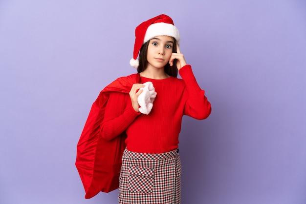 Маленькая девочка в шляпе и рождественском мешке изолирована на фиолетовой стене, думая об идее