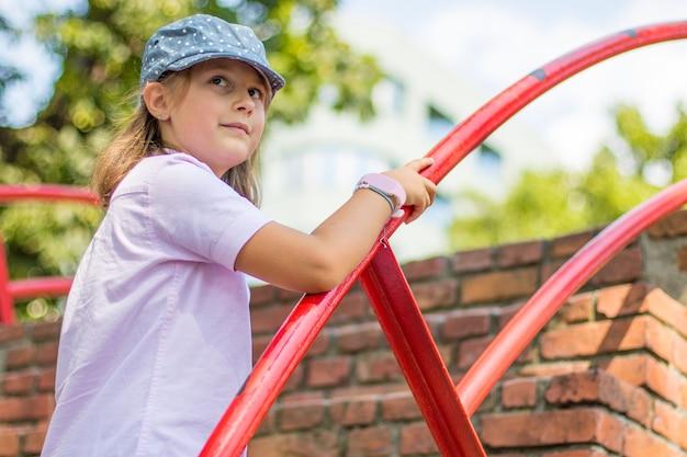 Маленькая девочка в шляпе поднимается по кирпичной лестнице