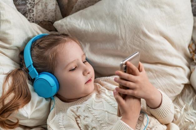 Маленькая девочка с наушниками и держит смартфон в руках лежит на диване