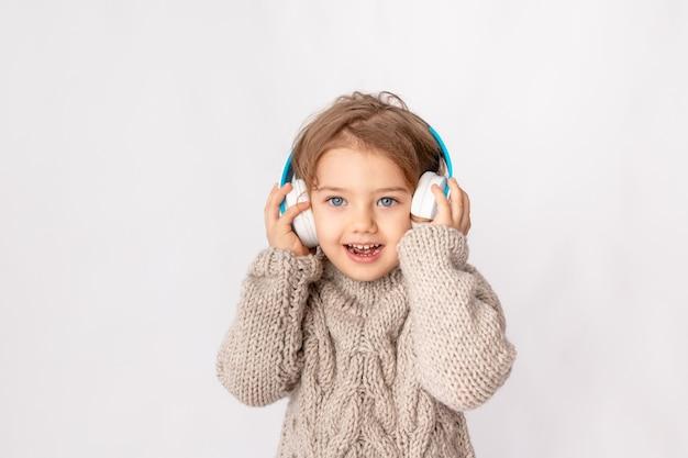 Маленькая девочка с наушниками на белом фоне, слушая музыку и наслаждаясь пространством для текста