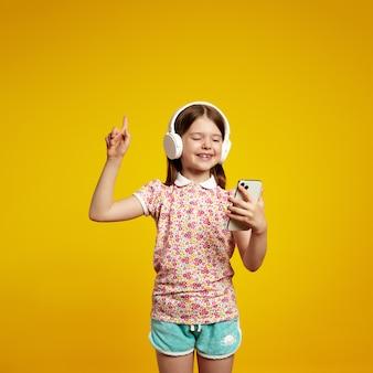 Маленькая девочка с наушниками, указывая указательным пальцем вверх, держа мобильный телефон