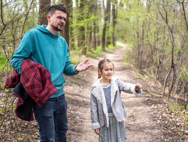 A little girl with her dad are walking in the spring forest and discussing something.