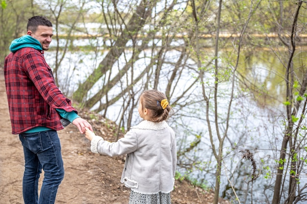 A little girl with her dad in early spring, in cold weather, walk near the river, holding hands.