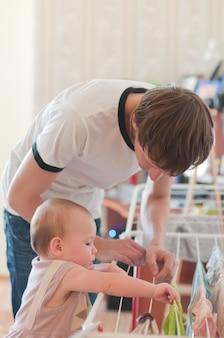 Маленькая девочка с отцом возле белья, снимающего одежду
