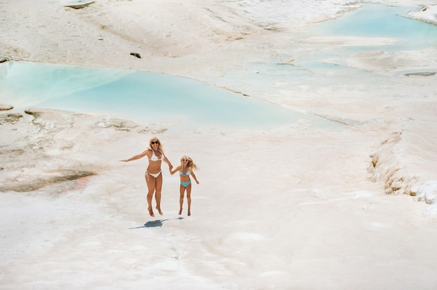 A little girl with her mother in bathing suits and sunglasses on a white mountain