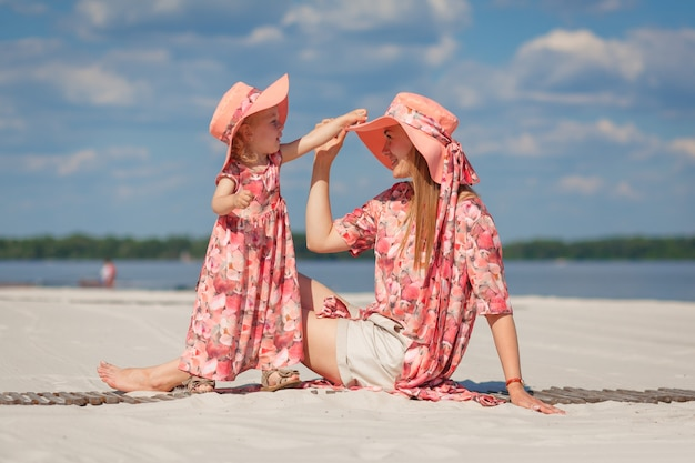 A little girl with her mother in matching beautiful sundresses plays in the sand on the beach. stylish family look.