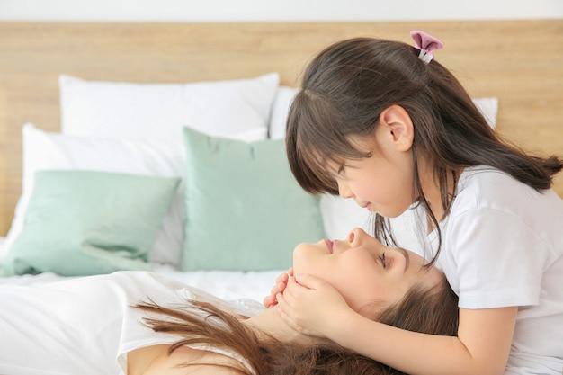 自宅のベッドで母親と一緒に小さな女の子