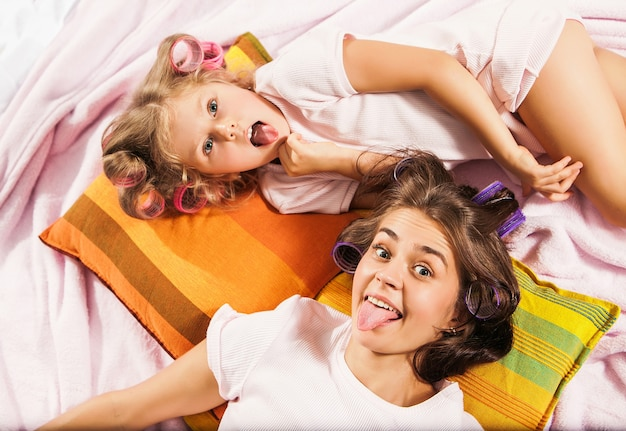 Little girl with her mother playing in bed