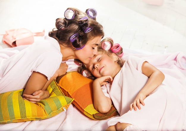 Little girl with her mother slipping in bed