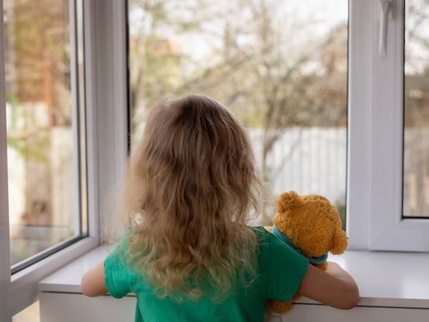 A little girl with her teddy bear looks out the window at the garden stay home concept
