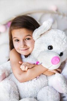ベッドに座っている彼女のテディを持つ少女。家、快適さ、家族、人間関係、人々