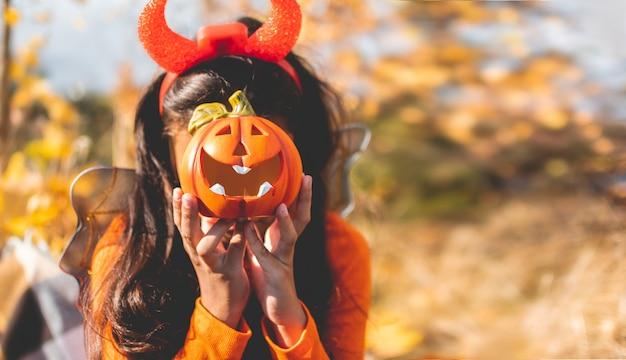 Маленькая девочка с фонарем jack o 'в шляпе ведьмы с тыквой.