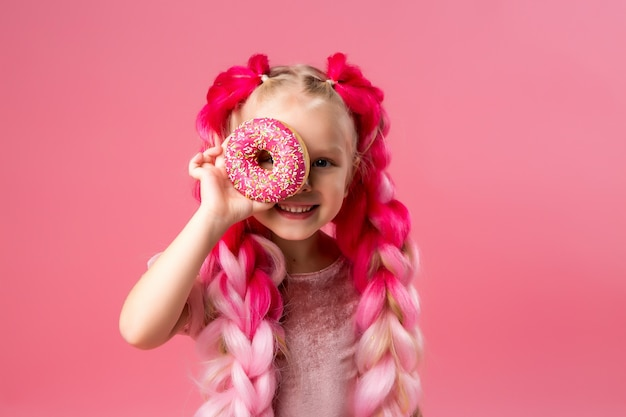 Little girl with kanekalon braids with donuts on pink background