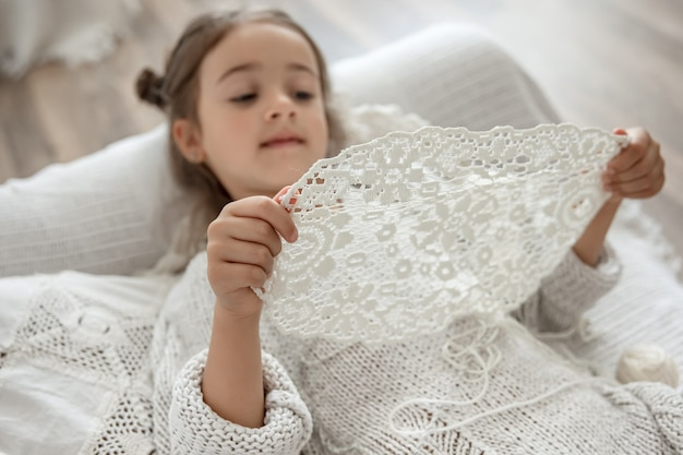 Little girl with a lace napkin from natural cotton yarn, crochet by hand. crochet as a hobby.