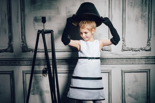 ドレスのランプシェードの帽子を持つ少女。エレガントで華やかなドレスと手袋をした子供。レトロな女の子、ファッションモデル、美容。レトロ、理髪店、化粧、ピンナップ。ファッション、ピンナップスタイル、子供時代